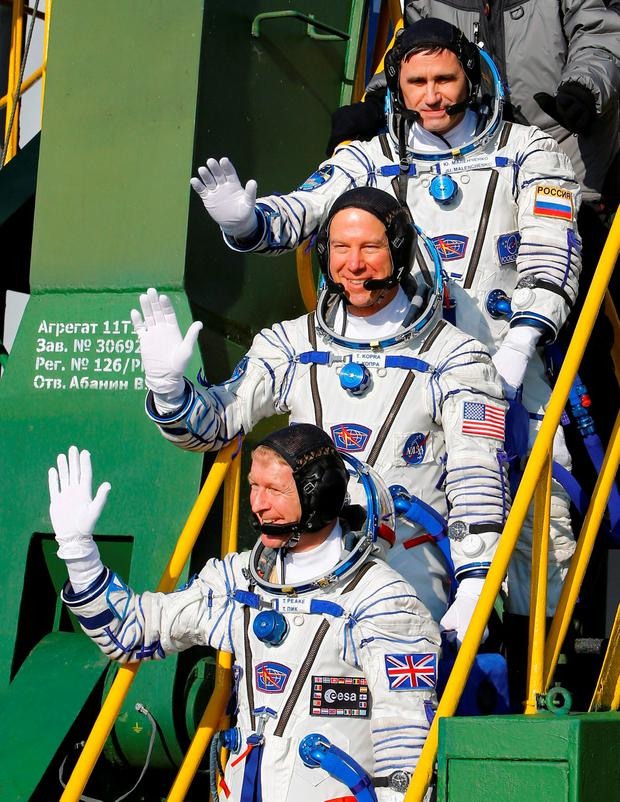 British astronaut Tim Peake, bottom, Russian cosmonaut Yuri Malenchenko, above, and U.S. astronaut Tim Kopra, members of the main crew of the mission to the International Space Station (ISS), gesture close to the rocket prior the launch at the Russian leased Baikonur cosmodrome, Kazakhstan, Tuesday, Dec. 15, 2015