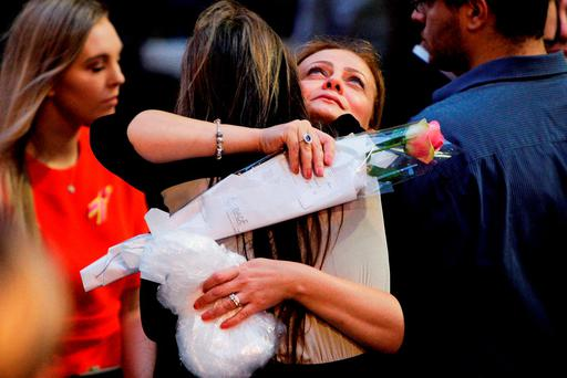 Lindt Cafe siege survivor Marcia Mikhael is embraced during a memorial ceremony commemorating the first anniversary of the Sydney cafe siege, in Martin Place, Australia. Reuters/Lisa Maree Williams/Pool