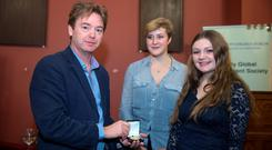 David McWilliams with Izzy Matushka, Chair of Trinity Global Development Society, and Annabel O'Rourke, Historical Society Correspondence Secretary, as he is honoured with the Gold Medal for Outstanding Contribution to Discourse through the Arts, in Trinity College Dublin. Photo: Arthur Carron