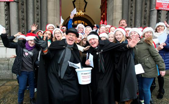 Rev. Canon David Gillespie (right), Vicar of St Ann's Church, Dawson Street, Dublin, with caretaker Fred Deane (left) and pupils from Castleknock National School at the annual 'Black Santa' Christmas Carols Appeal outside the church yesterday. Photo: Tom Burke