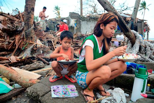 Residents eat outside their damaged shanties after typhoon Melor battered central Philippines. Photo: Renelyn Loquinario/Reuters