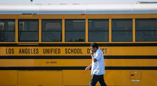 A Los Angeles Unified School District bus driver walks past parked vehicles at a bus garage in Gardena, Calif., on Tuesday, Dec. 15, 2015.
