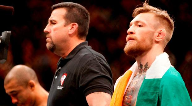 Conor McGregor (R) waits for the official announcement of his victory after a first-round knockout over Jose Aldo in their featherweight title fight during UFC 194 at MGM Grand Garden Arena on Saturday