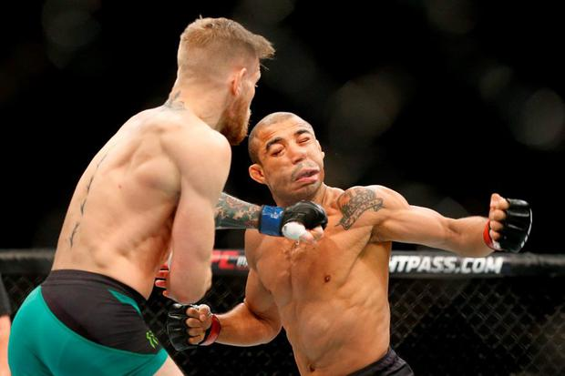 Conor McGregor, left, knocks out Jose Aldo during their UFC featherweight title bout at UFC 194