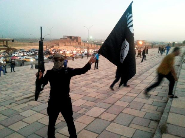 An Isil fighter waves a flag on a street in the city of Mosul, Iraq. Photo: Reuters