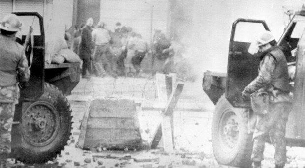 File photo dated 30/1/1972 of soldiers taking cover behind their sandbagged armoured cars while dispersing rioters with CS gas during protests in Londonderry, as former paratroopers who face questioning over Bloody Sunday have won their High Court battle against being detained and transferred to Northern Ireland for interview by police