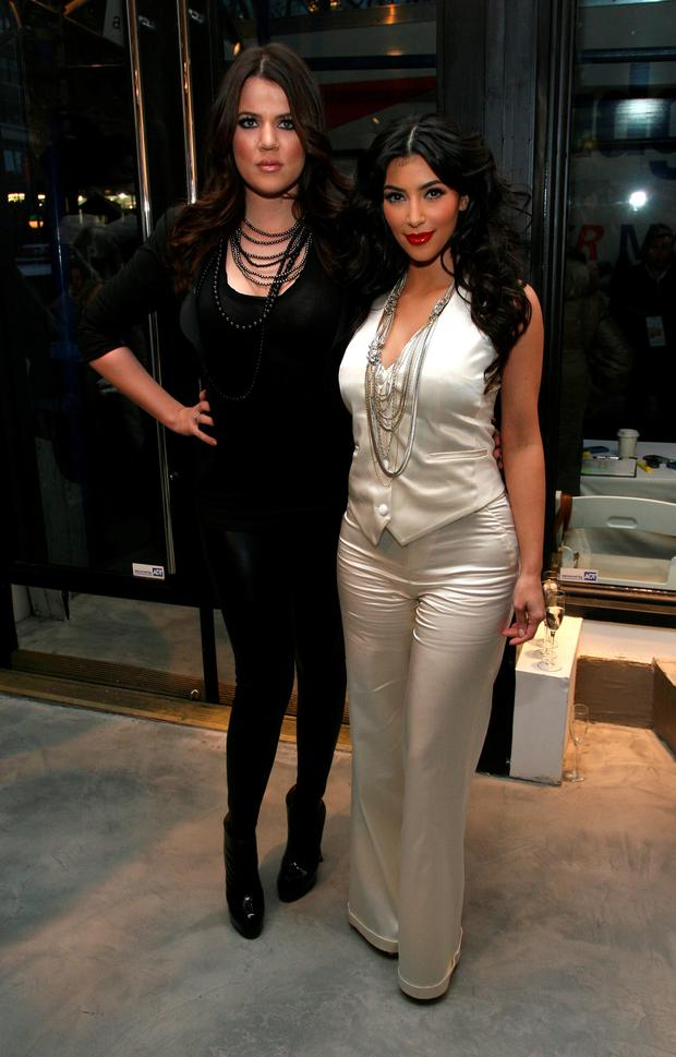 February 2009: Khloe Kardashian and Kim Kardashian pose at Payless at Alice + Olivia Fall 2009 show during Mercedes-Benz Fashion Week