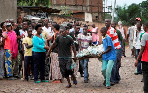 Men carry away a dead body in the Nyakabiga neighborhood of Bujumbura, Burundi Credit: AP Photo
