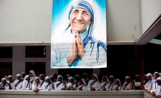 Catholic nuns from the order of the Missionaries of Charity gather under a picture of Mother Teresa during the tenth anniversary of her death in Kolkata, India, in this September 5, 2007. Reuters/Jayanta Shaw/Files