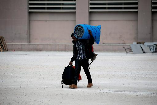 A migrant carries his belongings as he leaves the Tae Kwon Do stadium at the southern suburb of Faliro in Athens, Greece, December 16, 2015. Reuters/Alkis Konstantinidis