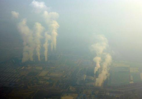 An aerial view shows smoke billowing from chimneys of factories located near Beijing, amid heavy smog under a red alert for air pollution, China. Reuters/Stringer