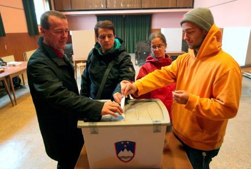 Family members cast ballots at a polling station during a referendum on whether to give same-sex couples the right to marry and to adopt children, in Sora, Slovenia December 20, 2015. REUTERS/Srdjan Zivulovic
