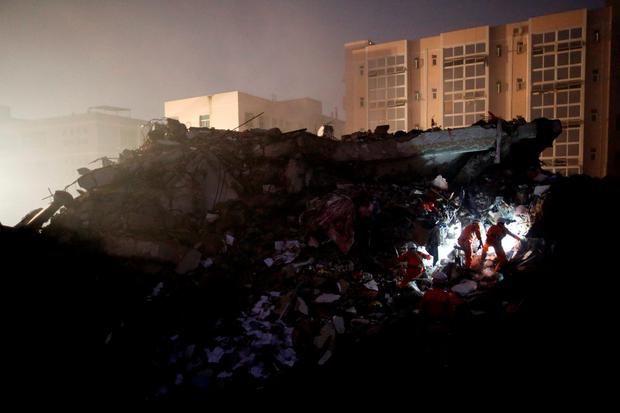 Firefighters use flashlights to search for survivors among the rubble of collapsed buildings after a landslide hit an industrial park in Shenzhen, Guangdong province, China December 20, 2015. REUTERS/Tyrone Siu