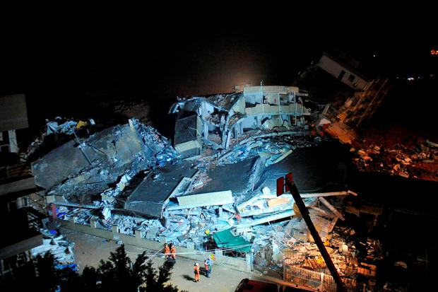 Firefighters stand next to collapsed buildings after a landslide hit an industrial park in Shenzhen, Guangdong province, China December 20, 2015