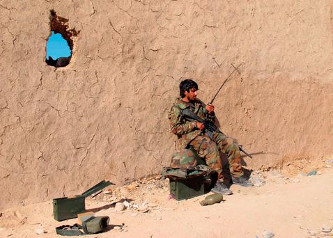 An Afghan National Army (ANA) soldier speaks on a radio at an outpost in Helmand province, December 20, 2015
