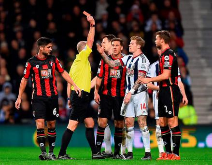 west Brom's James McClean (3rd R) is shown a red card by referee Mike Dean (2nd L) after fouling Adam Smith