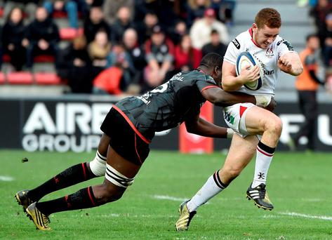Paddy Jackson tries to escape the clutches of Toulouse flanker Yacouba Camara. Photo: Sportsfile