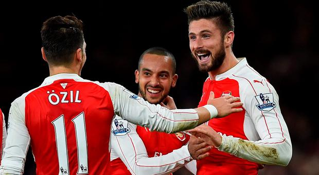 Olivier Giroud celebrates with Theo Walcott and Mesut Ozil after scoring Arsenal's second goal against Manchester City at the Emirates last night