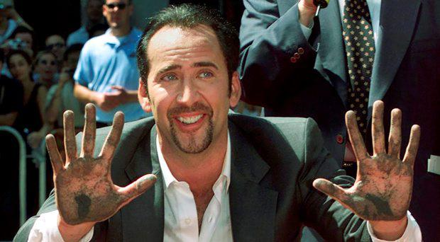 Actor Nicholas Cage smiles after placing his handprints in the forecourt at Grauman's Chinese Theater in Hollywood in this file photo taken August 14, 2001. Cage has agreed to forfeit a rare stolen dinosaur skull he bought for $276,000 to U.S. authorities so it can be returned to the Mongolian government