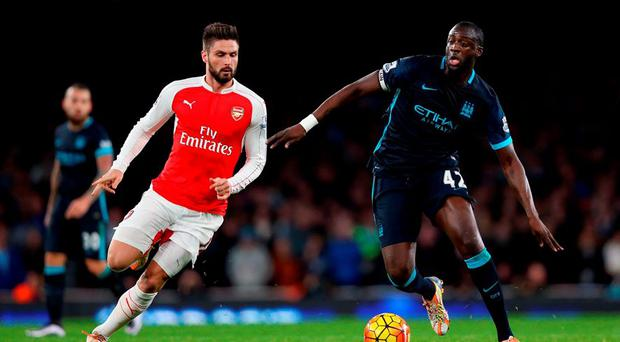 Olivier Giroud and Manchester City's Yaya Toure battle for the ball at The Emirates Stadium,
