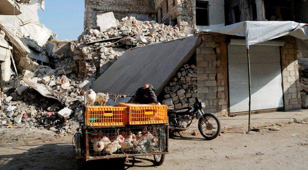A street vendor sells chicken in front of damaged buildings in Syria