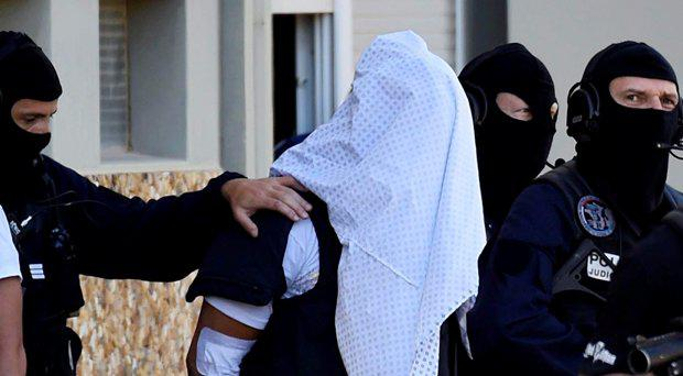 French police escort Yassin Salhi (C), a man suspected of decapitating his boss in an attack on a gas factory, as they leave his flat in Saint-Priest