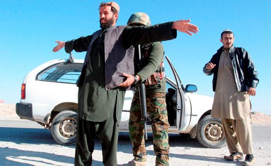An Afghan National Army soldier searches a passenger at a checkpoint on the way to the Sangin district of Helmand province, Afghanistan. Photo: AP