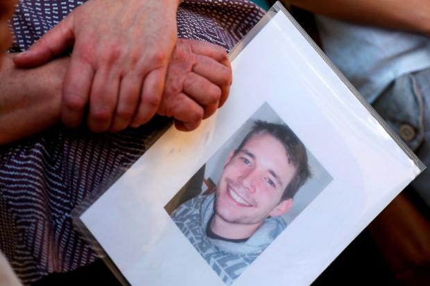 A family member holds a picture of David Miller, one of the two British tourists killed on Koh Tao island, while speaking to the media after hearing the verdict at the Koh Samui provincial court in Koh Samui, Thailand, December 24, 2015