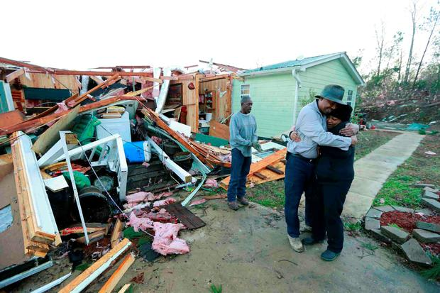Phyllis Evans gets a hug from Harvey Payne early Thursday morning after he stopped by to check on her and her home after a tornado struck Holly Springs, Mississippi, December 24, 2015. Southern U.S. states began digging out on Thursday after severe storms killed at least 11 people, and Mississippi declared a state of emergency in areas pounded by tornadoes. REUTERS/Northeast Mississippi Daily Journal/Thomas Wells