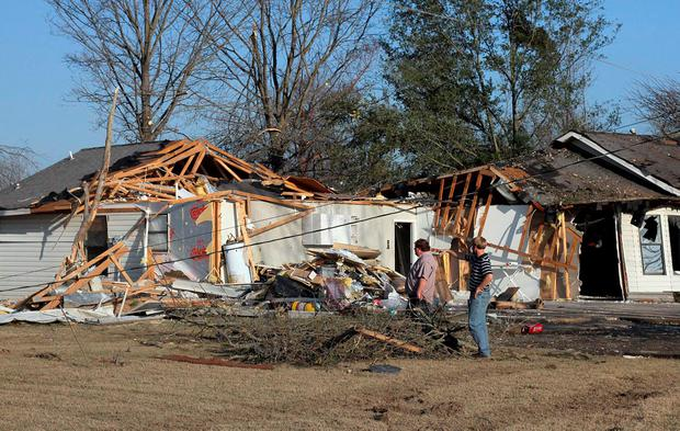 Alan Freeman and Brandon Schmidt (L to R) assess the damage to Brandon's brother's home after a powerful tornado struck Clarksdale, Mississippi, December 24, 2015. Southern U.S. states began digging out on Thursday after severe storms killed at least 11 people, and Mississippi declared a state of emergency in areas pounded by tornadoes. REUTERS/Justin A. Shaw