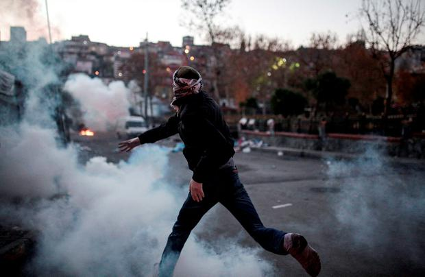 A masked man throws a petrol bomb toward police using water cannon and teargas to disperse people protesting against security operations against Kurdish rebels in southeastern Turkey, in Istanbul, Sunday, Dec. 20, 2015. (AP Photo/Cagdas Erdogan)