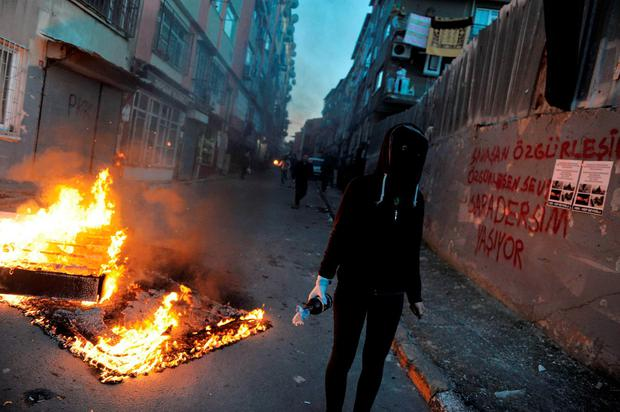 A masked man waits to throw a petrol bomb toward police who used water cannons and teargas to disperse people protesting against security operations against Kurdish rebels in southeastern Turkey, in Istanbul, Sunday, Dec. 20, 2015. (AP Photo/Omer Kuscu)