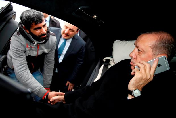 Turkish President Recep Tayyip Erdogan, right, takes Vezir Cakras by hand while speaking on his mobile phone inside his car stationed over the Bosporus Bridge in Istanbul, Friday, Dec. 25, 2015. (Yasin Bulbul/Presidential Press Service Pool via AP Photo )
