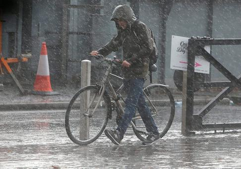 A man gets caught in heavy rain in stormy conditions in Dublin city centre. Picture credit: Damien Eagers