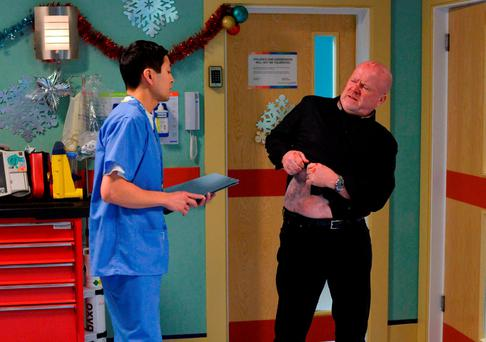 Dr Yip examining a reluctant Phil Mitchell played by Steve McFadden (right) where he is told he has cirrhosis of the liver. Picture: Kieron McCarron/BBC/PA Wire