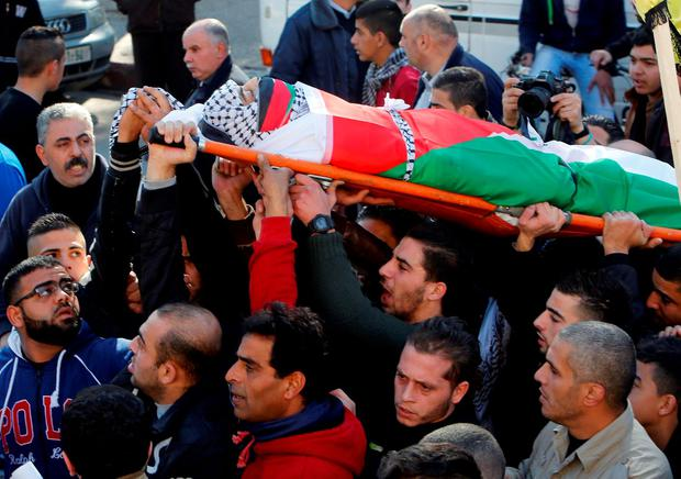 Mourners carry the body of Palestinian Maher Aljabi, 56, whom medics said was shot and killed by Israeli troops on Saturday, during his funeral in the West Bank city of Nablus December 27, 2015. REUTERS/Abed Omar Qusini