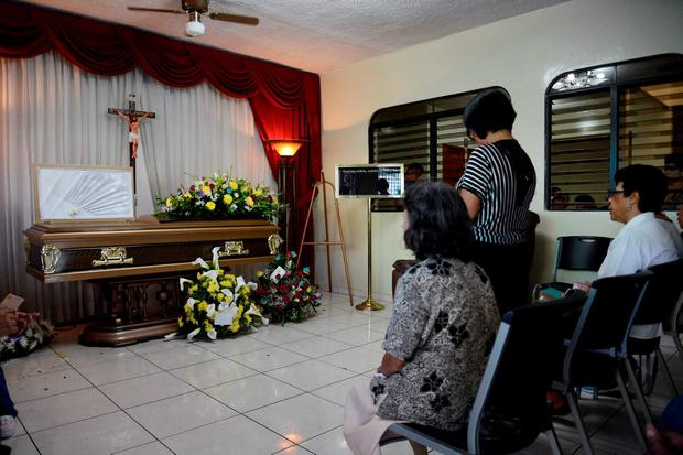 Relatives are seen next to a coffin with the body of Alfredo Pacheco during his wake in Santa Ana, El Salvador. REUTERS/Jessica Orellana