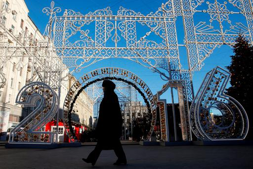 A woman walks past a New Year's decoration in central Moscow yesterday. Photo: Maxim Zmeyev