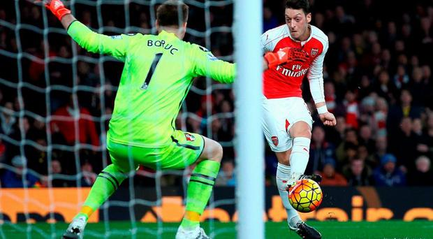 Mesut Ozil fires the ball past Artur Boruc to score Arsenal's second goal. Photo: Ian Walton/Getty Images