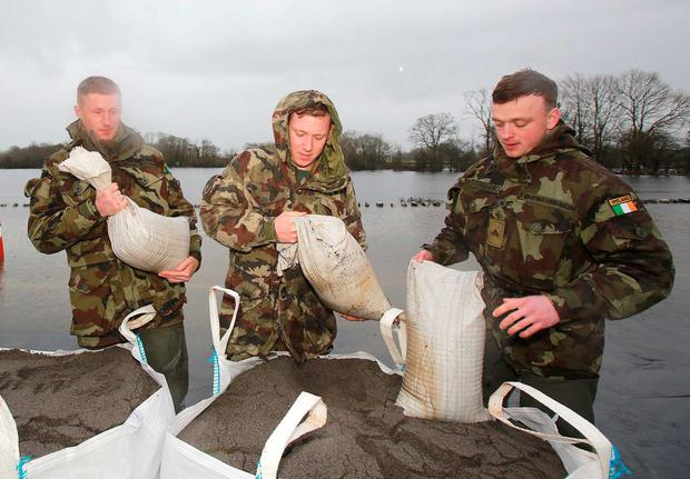 Members of the Army's 2nd Battalion fill sandbags in Laban, Co Galway, to help hold back rapidly rising floodwaters. Picture: Hany Marzouk