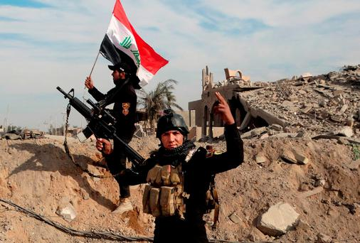 Iraqi security forces raise an Iraqi flag near the provincial council building in central Ramadi. AP Photo/Osama Sami