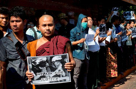 Protestors, including a Buddhist monk, display placards close to the Thai Embassy in Yangon, Myanmar (AP Photo/Gemunu Amarasinghe)