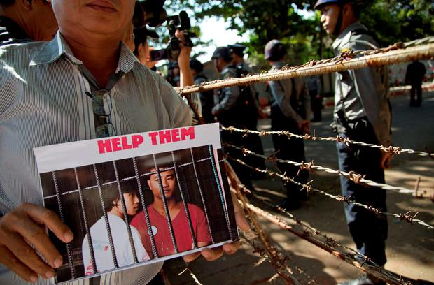 A protestor displays a picture featuring Myanmar migrants Win Zaw Htun, right, and Zaw Lin near the Thai Embassy in Yangon, Myanmar (AP Photo/Gemunu Amarasinghe)