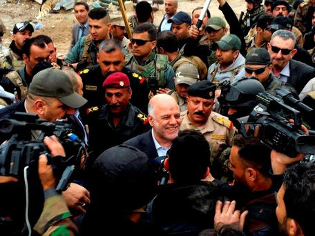 Iraqi Prime Minister Haider al-Abadi, center, smiles as he tours the city of Ramadi after it was retaken by security forces. Photo: AP