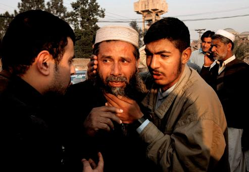 People comfort a man who lost a family member in a suicide attack in Mardan, Pakistan. Photo: AP
