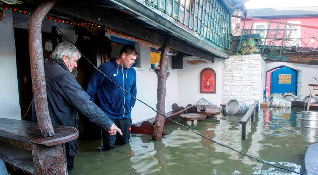 Publican Donal and son Damien Crowley of Buckleys Bar stands in flood waters in his Beer Garden in Bandon, co. Cork during heavy flooding.
