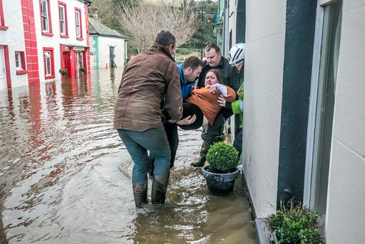 Maureen Dowd is rescued from her home in Inistioge, Co Kilkenny, during severe flooding in the picturesque village. Photo: Pat Moore