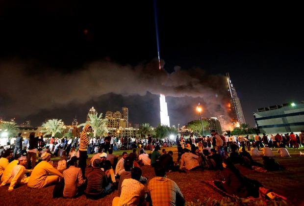 A picture taken on December 31, 2015 shows people watching the Address Downtown hotel burning after huge fire ripped through the luxury hotel near the world's tallest tower, in Dubai. People were gathering to watch New Year's Eve celebrations when the hotel caught on fire without causing casualties, according to authorities