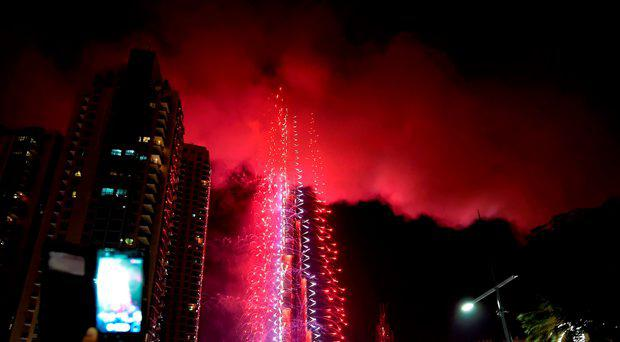 Smoke billows from the Address Downtown Hotel, after it caught on fire hours earlier, past fireworks, near the Burj Khalifa, the world's tallest tower in Dubai, on January 1, 2015