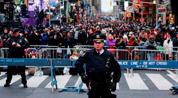 NEW YORK, NY - DECEMBER 31: A New York Police officer stands guard as people go in to Times Square prior to the Times Square new years eve celebration on December 31, 2015 in New York City. The New York Police Department will have more than 6,000 officers in the Times Square area, including more than 1,100 officers who graduated from the police academy on Tuesday. It will be the largest such deployment of police in New York City ever. (Photo by Eduardo Munoz Alvarez/Getty Images)